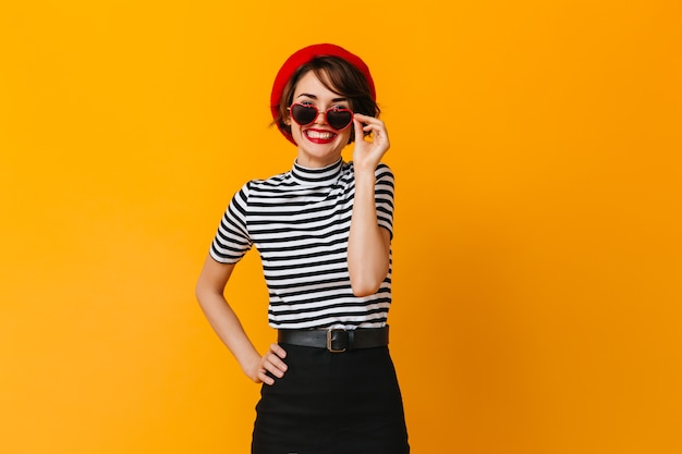 Ecstatic french woman wearing beret and heart-shaped sunglasses