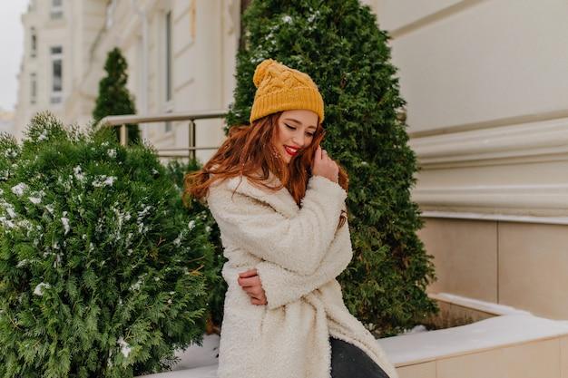 恍惚とした生姜の女の子が誠実な笑顔でモミの近くでポーズをとる。屋外に立っている白いコートを着た楽しいヨーロッパの女性。