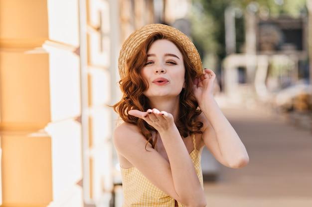도시에 공기 키스를 보내는 황홀한 생강 아가씨. 좋은 하루에 편안한 여름 모자에 사랑스러운 red-haired 소녀.