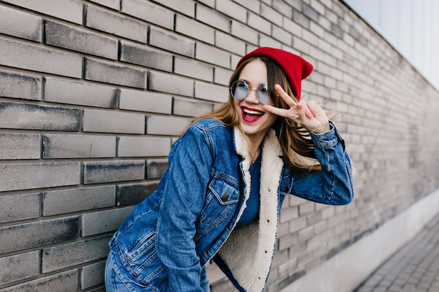 春の日のレンガの壁の近くでポーズをとって面白いデニムの衣装で恍惚とした女の子。ピースサインと通りに立っている陽気な白人女性モデルの肖像画。
