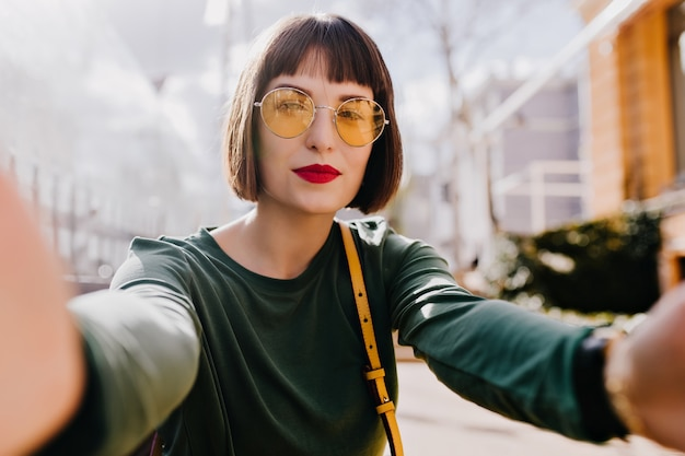 Восторженная девушка в желтых очках делает селфи с серьезным выражением лица. открытый выстрел довольной женщины брюнетки в зеленом свитере фотографируя на городе.