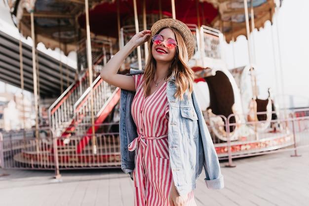황홀한 소녀는 진지한 미소로 회전 목마 근처에서 포즈를 취하는 데님 재킷을 입습니다. 놀이 공원에서 하루를 보내는 스트라이프 드레스에 귀여운 금발 여자의 야외 사진.