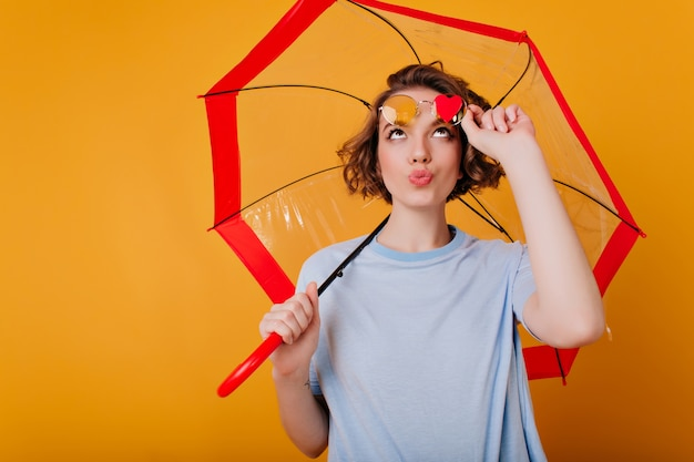 Ecstatic girl with funny face expression touching her sunglasses and looking at little heart. indoor photo of inspired young brunette woman posing with umbrella.