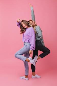 Ragazze estatiche in abiti alla moda che si godono i ritratti. modello femminile entusiasta che esprime emozioni positive e sorridente.