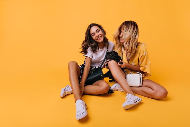 Le ragazze estatiche indossano scarpe di gomma che posano sul giallo. modelli femminili accattivanti seduti con le gambe incrociate mentre giocano con il bulldog francese.