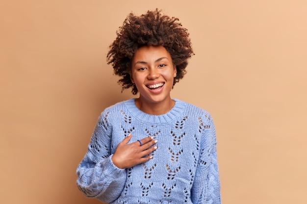 巻き毛のアフロ髪の恍惚としたうれしそうな若い女性が幸せに笑う青いセーターを着て明るい気分を持っているパーティーで友達と気軽に話し合う茶色の壁に孤立した前向きな感情を表現する