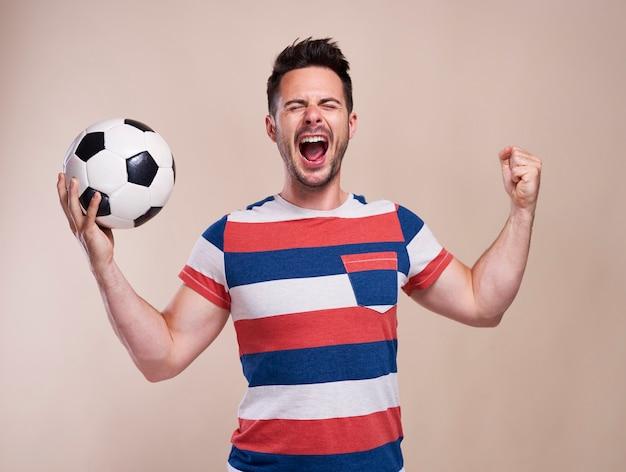 Восторженный мужской фанат с аплодисментами футбольного мяча
