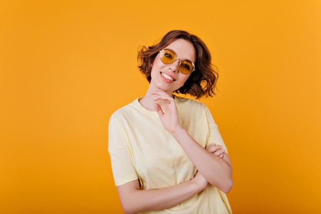 미소로 포즈를 취하는 빈티지 선글라스에 황홀한 창백한 소녀. 밝은 노란색 옷을 입은 화려한 여성 모델의 실내 사진.