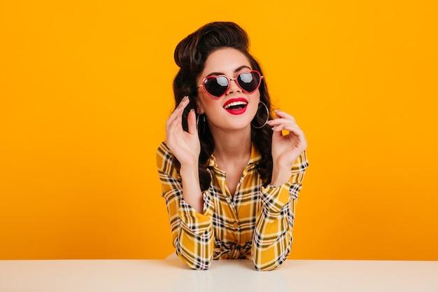 Ecstatic pinup girl posing in heart shaped glasses. studio shot of dreamy elegant woman in checkered shirt.