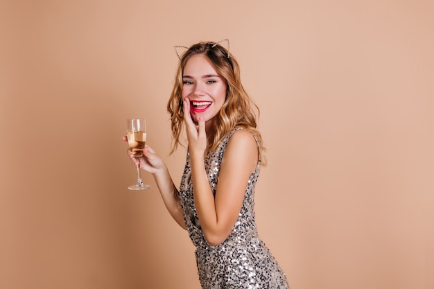 Ecstatic slim white woman covers mouth with hand, laughing at new year party