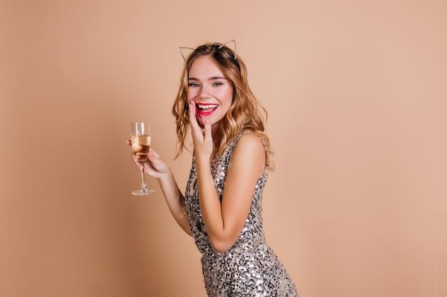 La donna bianca esile estatica copre la bocca con la mano, ridendo alla festa di capodanno