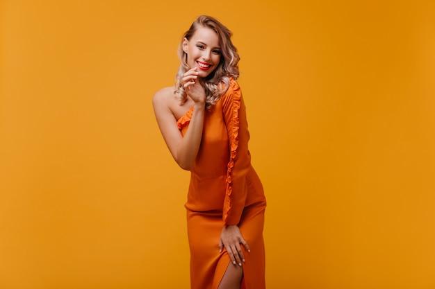 Восторженная улыбающаяся женщина в длинном платье позирует на желтой стене