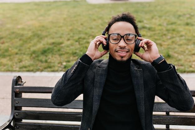 벤치에 앉아 우아한 정장에 황홀 할 정도로 세련 된 아프리카 남자. 잔디밭에 그의 헤드폰을 만지고 안경에 기쁘게 흑인 남자