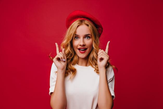 놀랍게도 포즈를 취하는 베레모에 황홀한 백인 소녀. 빨간 벽에 서있는 t- 셔츠에 우아한 백인 여성 모델.