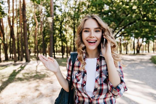숲에서 쉬고있는 동안 전화 통화 황홀 백인 여자. 물결 모양의 머리가 공원에서 걸어 다니는 즐거운 여자의 야외 사진.