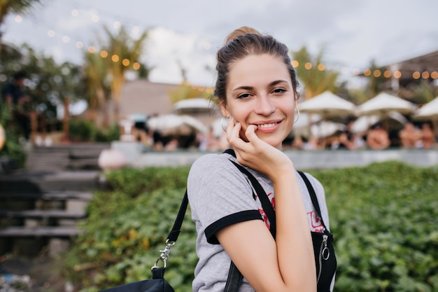 자연에 포즈를 취하는 동안 부드럽게 그녀의 얼굴을 만지고 황홀한 백인 여자. 리조트 시티에 서있는 매혹적인 아가씨의 야외 사진.
