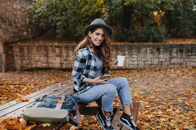 Восторженная белая женщина в винтажных джинсах сидит на деревянной скамейке в осенний день