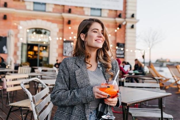 Восторженная женщина в сером пальто с улыбкой смотрит в сторону, попивая фруктовый напиток в кафе