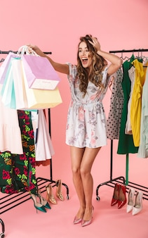 Восторженная женщина, стоящая в магазине возле вешалки для одежды и держащая красочные сумки для покупок, изолированные на розовом