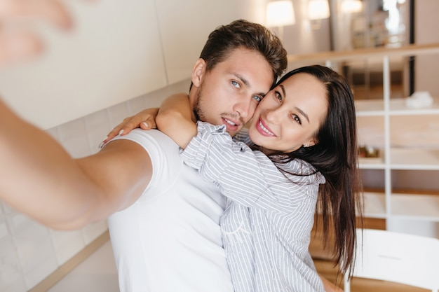 Ecstatic woman with brown eyes huggs with boyfriend while he making selfie