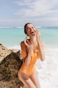 Восторженная женщина с искренним смехом позирует на пляже. стройная молодая леди в ретро желтом купальнике стоит рядом с морской скалой и улыбается.