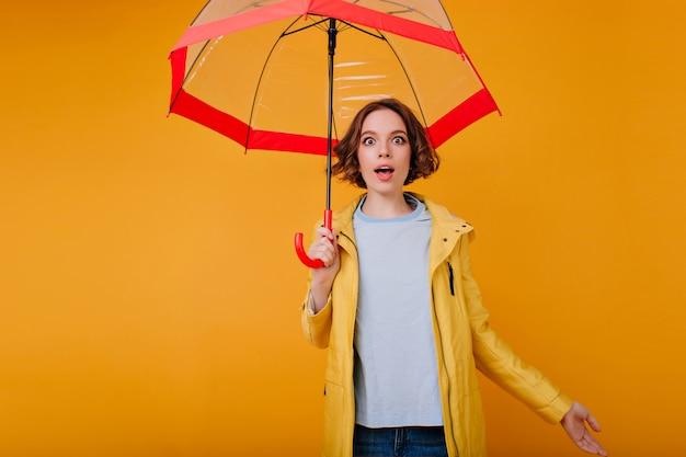 Giovane donna caucasica estatica in camicia blu e cappotto giallo che esprime stupore. foto dell'interno della ragazza sognante riccia che si diverte durante il servizio fotografico con l'ombrellone.