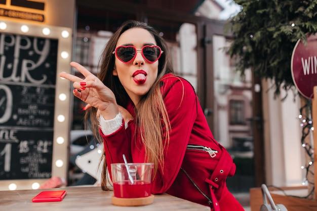 舌を出してポーズをとる赤い眼鏡の恍惚とした若い女性モデル