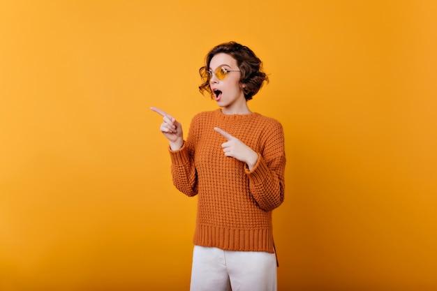 Восторженная молодая девушка с бледной кожей эмоционально позирует в круглых очках. беззаботная барышня в шерстяном наряде дурачится на фотосессии.