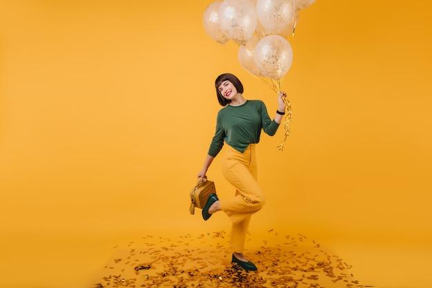 Восторженная барышня расслабляется в день рождения и с удовольствием позирует. портрет привлекательной кавказской девушки смешные танцы с воздушными шарами.