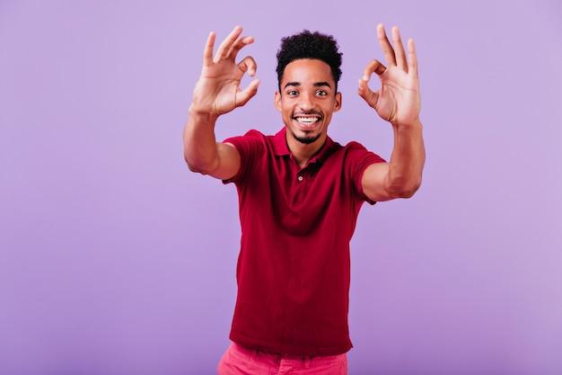 紫の壁に前向きな感情を表現する恍惚とした青年。黒髪の好奇心旺盛な男の笑顔の写真。