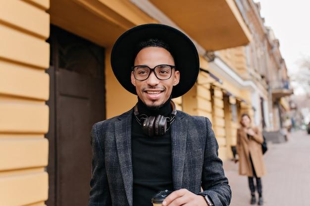 꿈꾸는듯한 미소로 멀리 보이는 갈색 피부를 가진 황홀한 젊은 남자. 레스토랑 근처에 서 잘 생긴 웃는 흑인 남자의 야외 초상화.