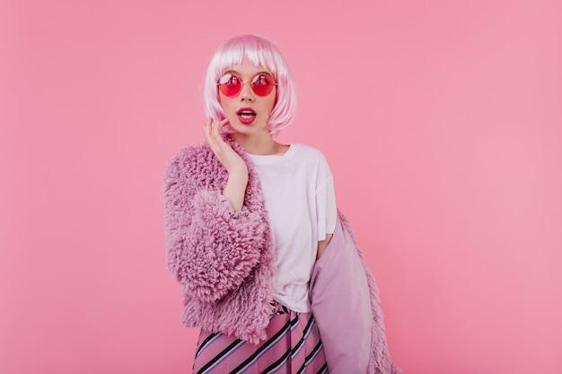 Giovane donna estatica in soffice giacca divertente in posa sulla parete rosa. ritratto dell'interno della ragazza caucasica gioconda stupefacente in periwig