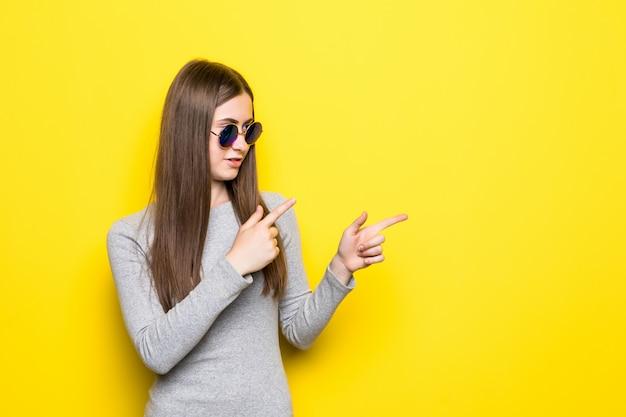 Восторженная молодая женщина в джинсовых шортах, белой рубашке и солнцезащитных очках, держа руку на бедре, глядя в сторону и указывая