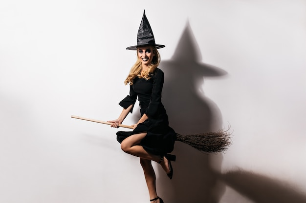 Ecstatic young woman in witch hat having fun in carnival. indoor photo of elegant caucasian girl sitting on magic broom.