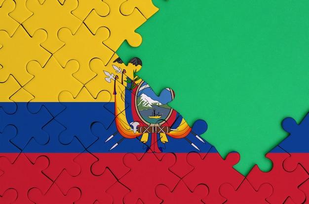 에콰도르 국기는 오른쪽에 무료 녹색 복사 공간이있는 완성 된 직소 퍼즐에 그려져 있습니다.