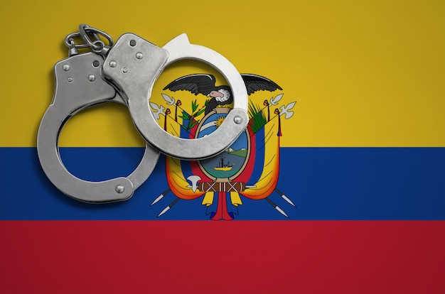 Ecuador flag  and police handcuffs. the concept of crime and offenses in the country