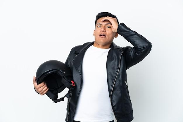 Экудорианский мужчина в мотоциклетном шлеме на белом фоне делает неожиданный жест, глядя в сторону