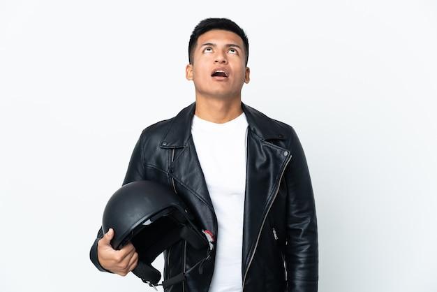 Экудорианский мужчина в мотоциклетном шлеме на белом фоне смотрит вверх и с удивленным выражением лица