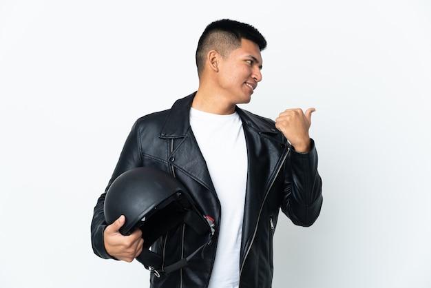 Экудорианский мужчина в мотоциклетном шлеме на белом фоне, указывая в сторону, чтобы представить продукт