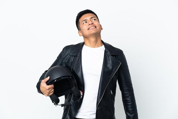 Экудорианский человек в мотоциклетном шлеме на белом фоне, думая об идее, глядя вверх