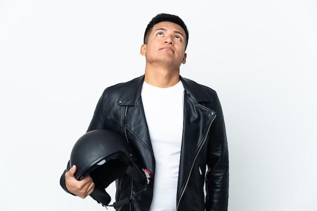 흰 벽에 고립 된 오토바이 헬멧을 가진 에콰도르 사람