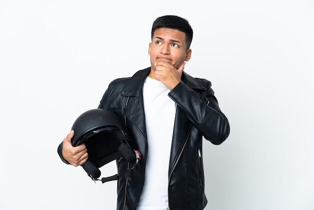 Экудорианский человек в мотоциклетном шлеме, изолированный на белой стене, сомневается и думает