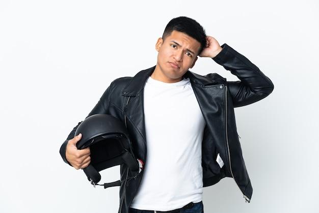 Экудорианский человек с мотоциклетным шлемом, изолированным на белой стене, сомневаясь