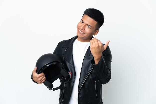 Экудорианский человек с мотоциклетным шлемом, изолированным на белой стене, приглашая прийти с рукой. счастлив что ты пришел