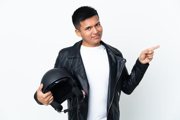 측면에 손가락을 가리키는 흰 벽에 고립 된 오토바이 헬멧 에콰도르 사람