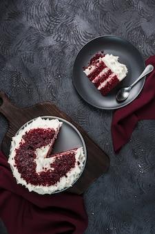 Ed velvet cake on dark background, flatlay top view.