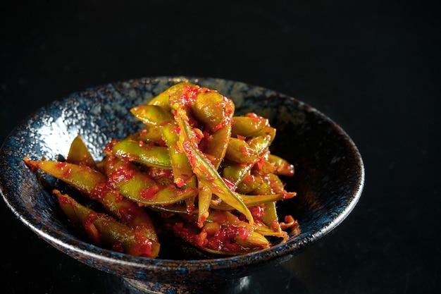 枝豆のスパイシーなレッドソースサラダ、ダークボウルでお召し上がりいただけます。黒いテーブルに隔離。レストランの食べ物。日本のキッチン