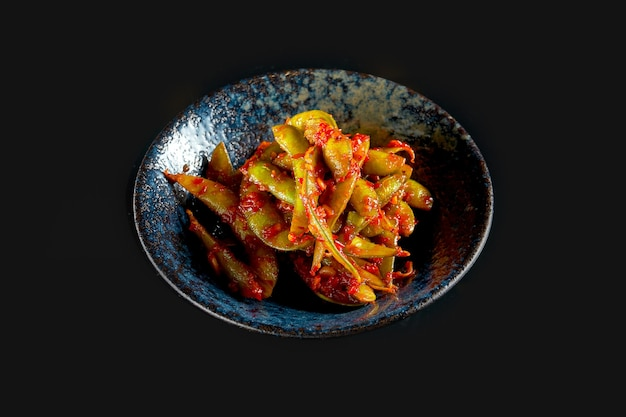 Edamame bean salad in a spicy red sauce served in a dark bowl
