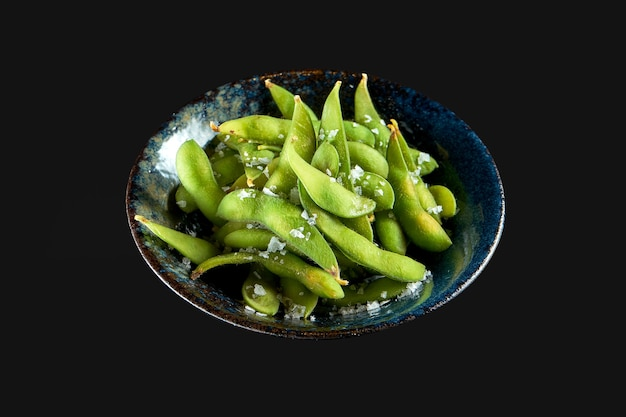 Edamame bean salad with sea salt served in a dark bowl isolated on a black background