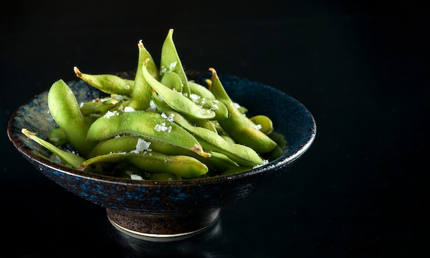 Edamame bean salad with sea salt served in a dark bowl. isolated on a black table. restaurant food. japanese kitchen